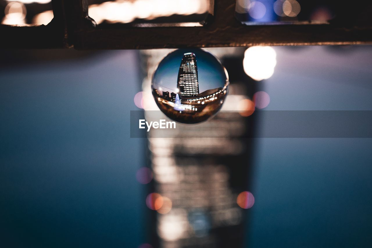 close-up, reflection, no people, focus on foreground, crystal ball, architecture, sphere, indoors, selective focus, glass - material, built structure, lighting equipment, illuminated, crystal, wealth, nature, water, building, luxury