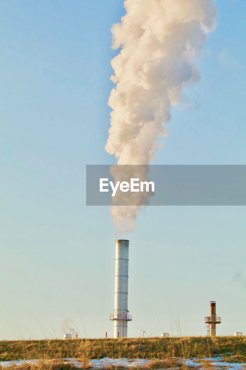 SMOKE EMITTING FROM CHIMNEY AGAINST THE SKY