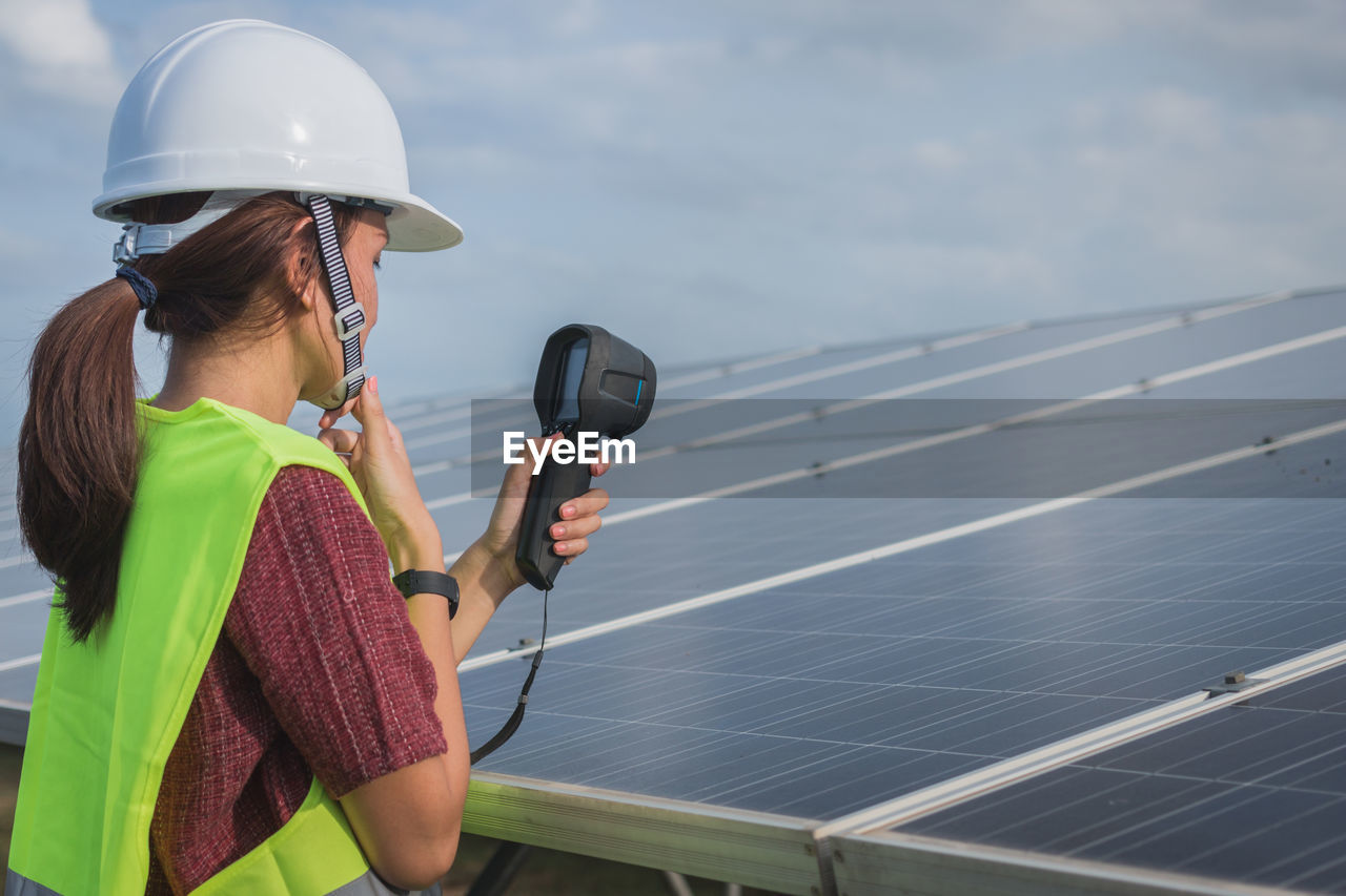 technology, helmet, women, one person, real people, adult, sky, alternative energy, nature, safety, renewable energy, young adult, solar panel, day, solar energy, hat, mode of transportation, fuel and power generation, lifestyles, wireless technology, outdoors
