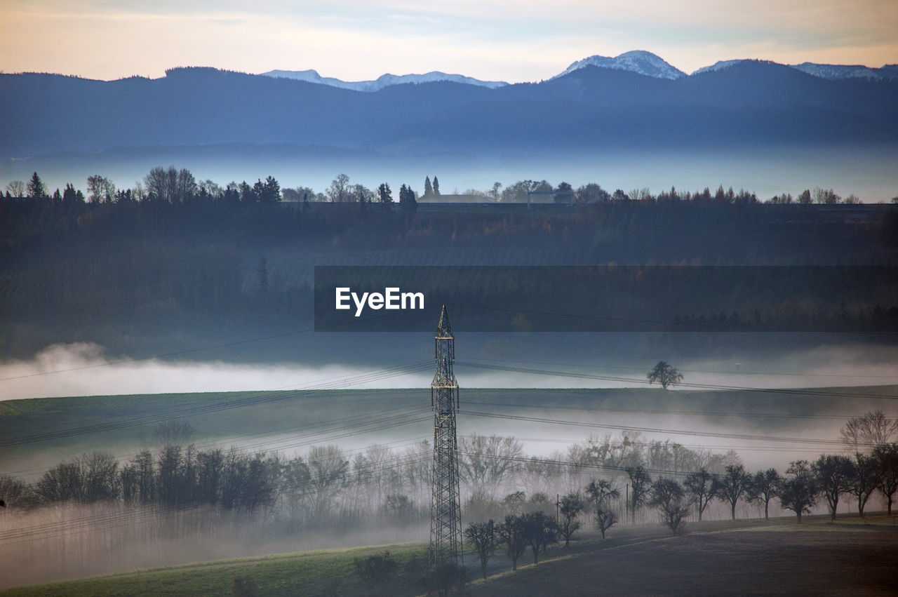 Electricity Pylon On Field Against Sky During Foggy Weather