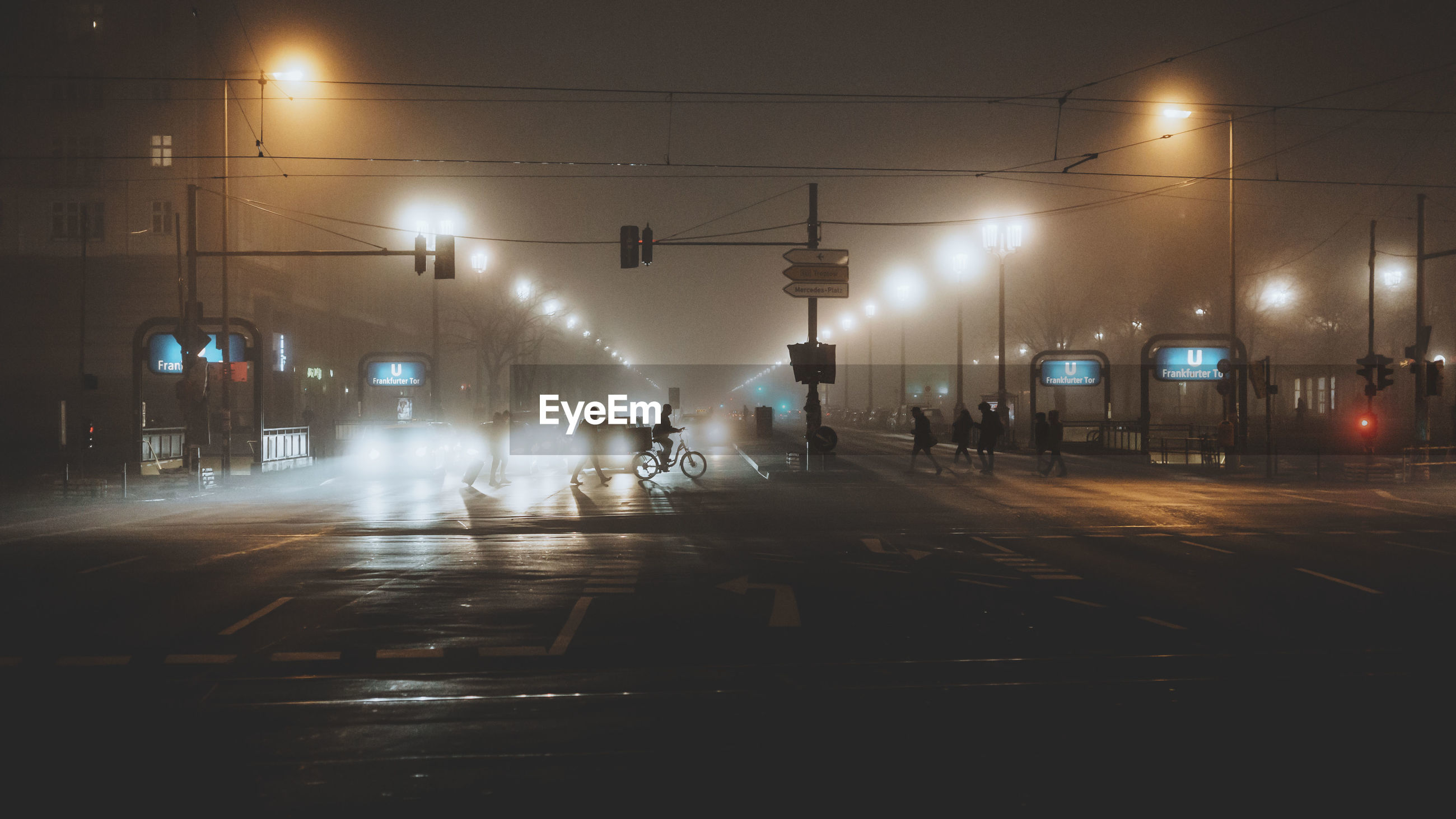 Silhouette people walking on illuminated street at night during foggy weather