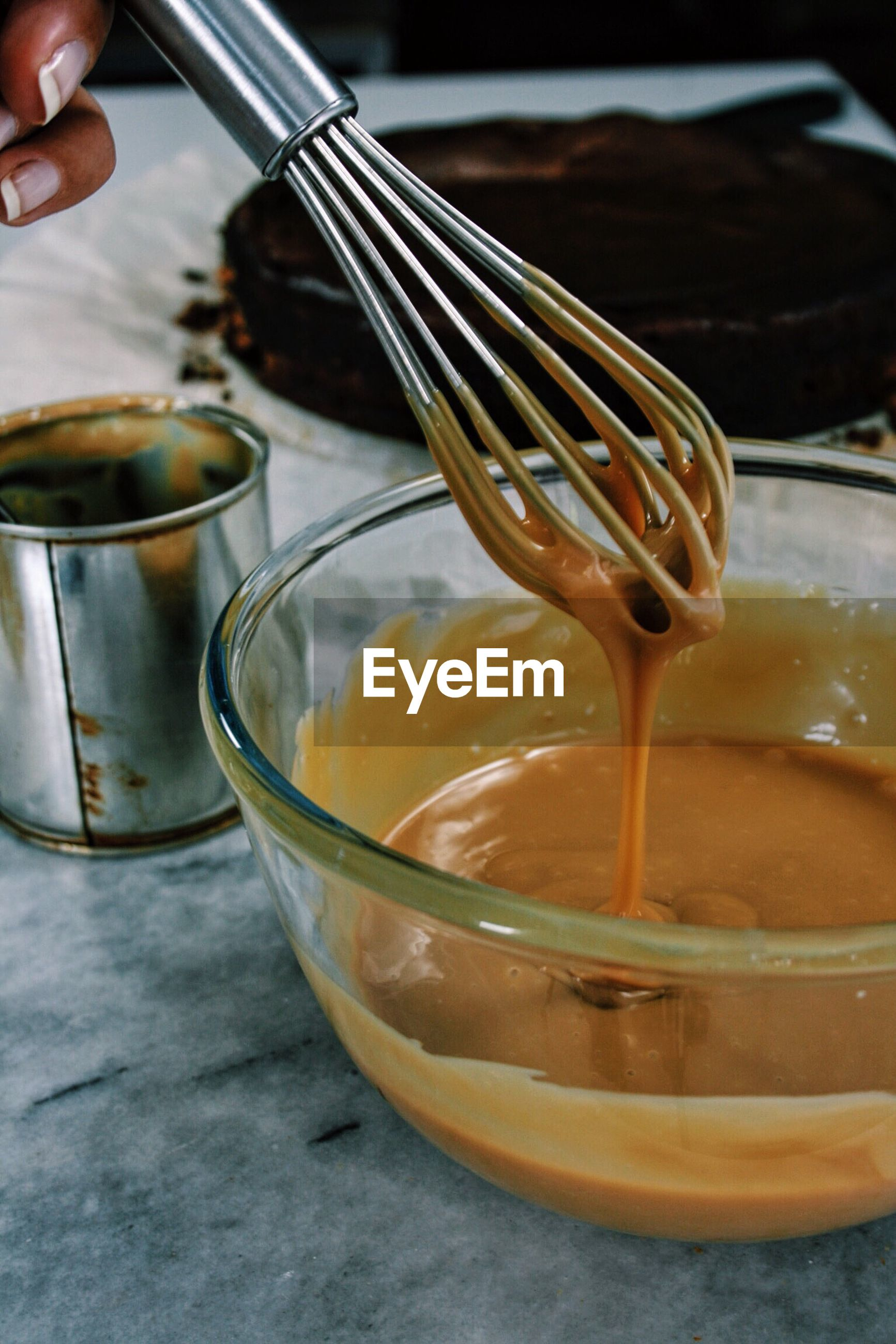 Cropped hand of woman mixing caramel