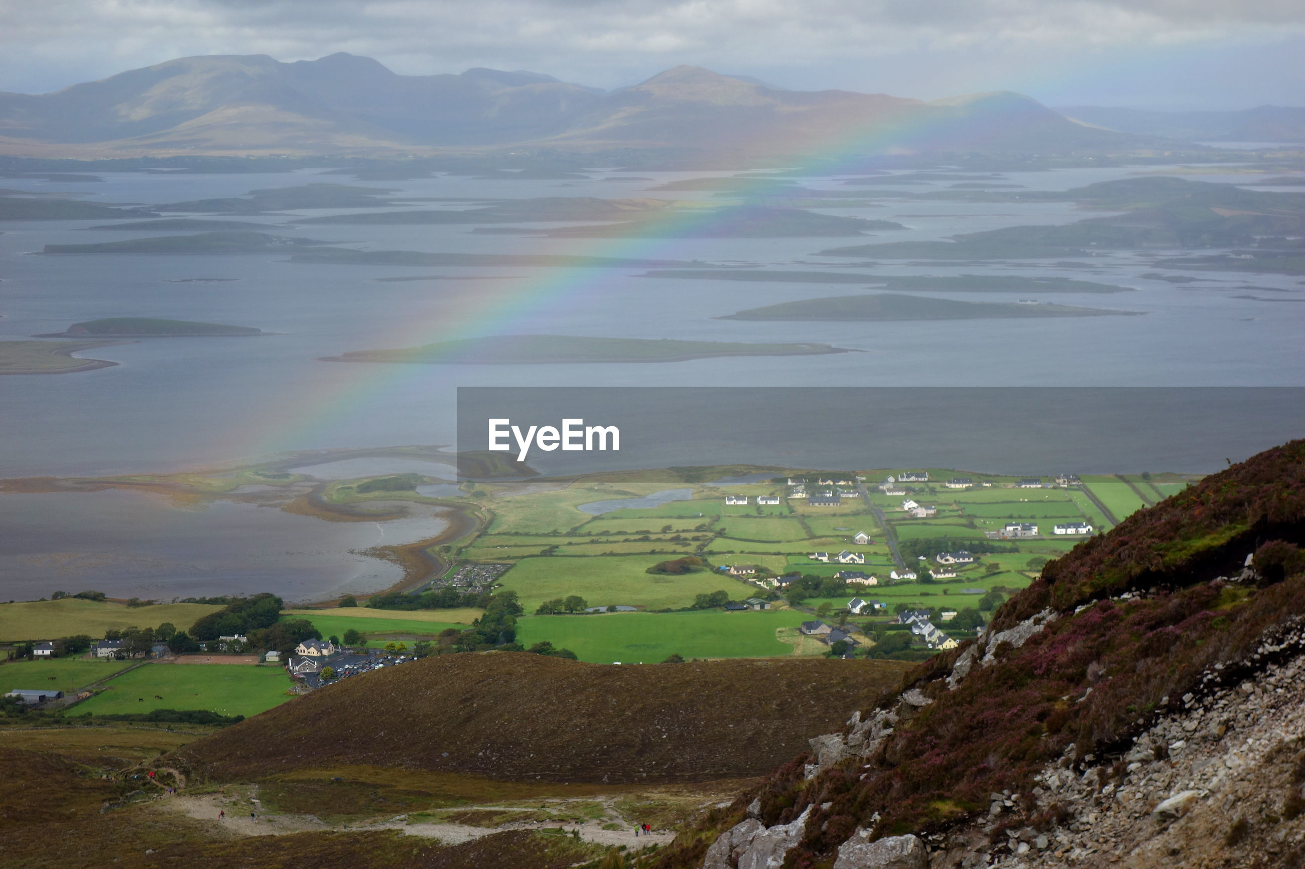SCENIC VIEW OF RAINBOW OVER LAND AND MOUNTAINS