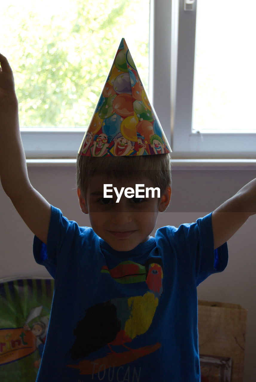 Portrait of cute boy wearing party hat at home
