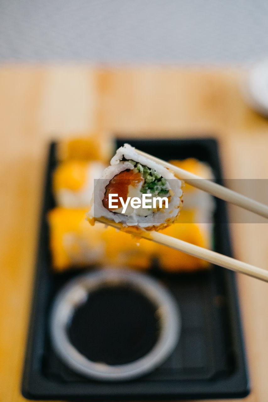 Close-Up Of Sushi In Chopsticks In Plate