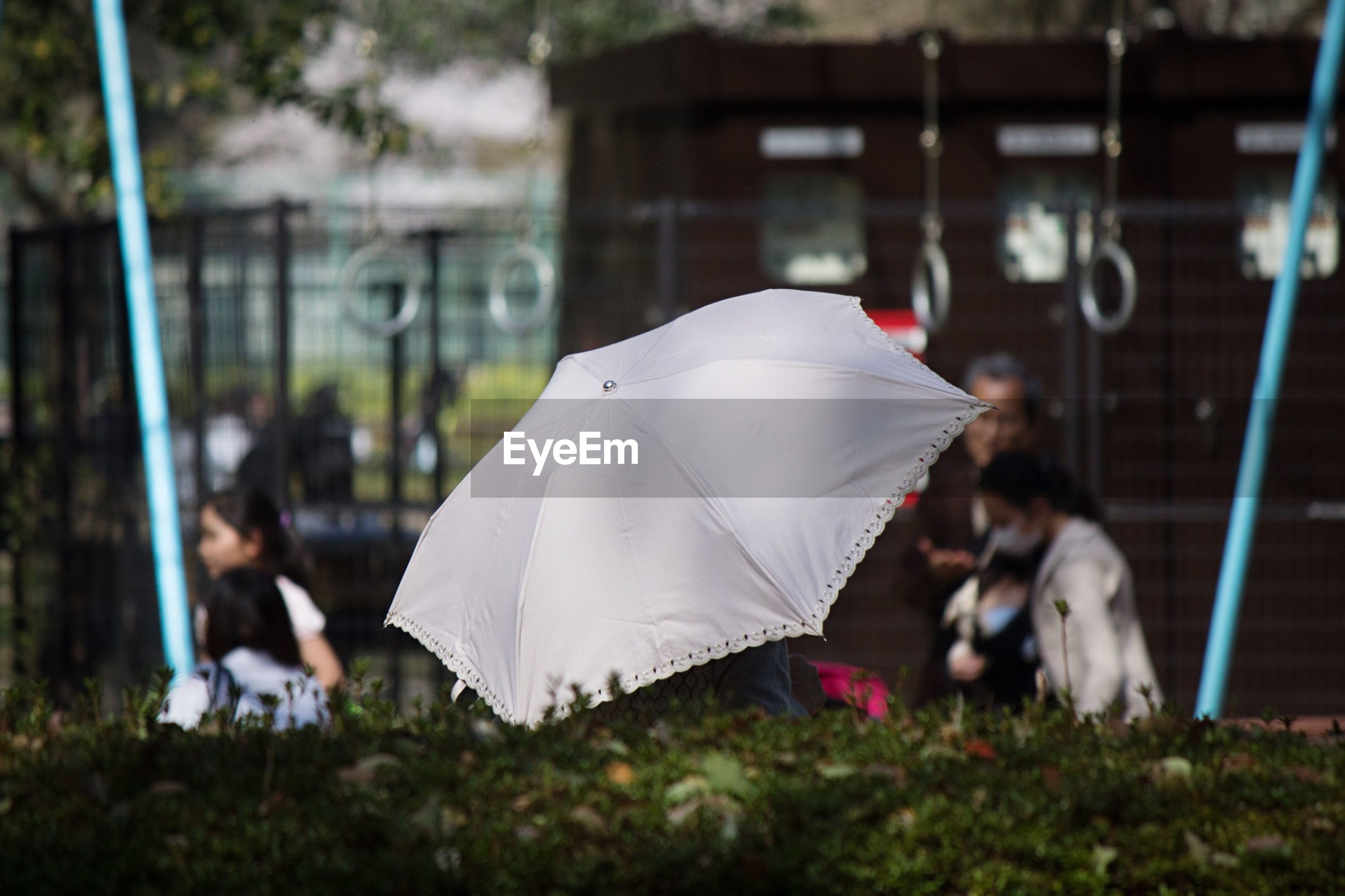 Open umbrella with children playing at playground