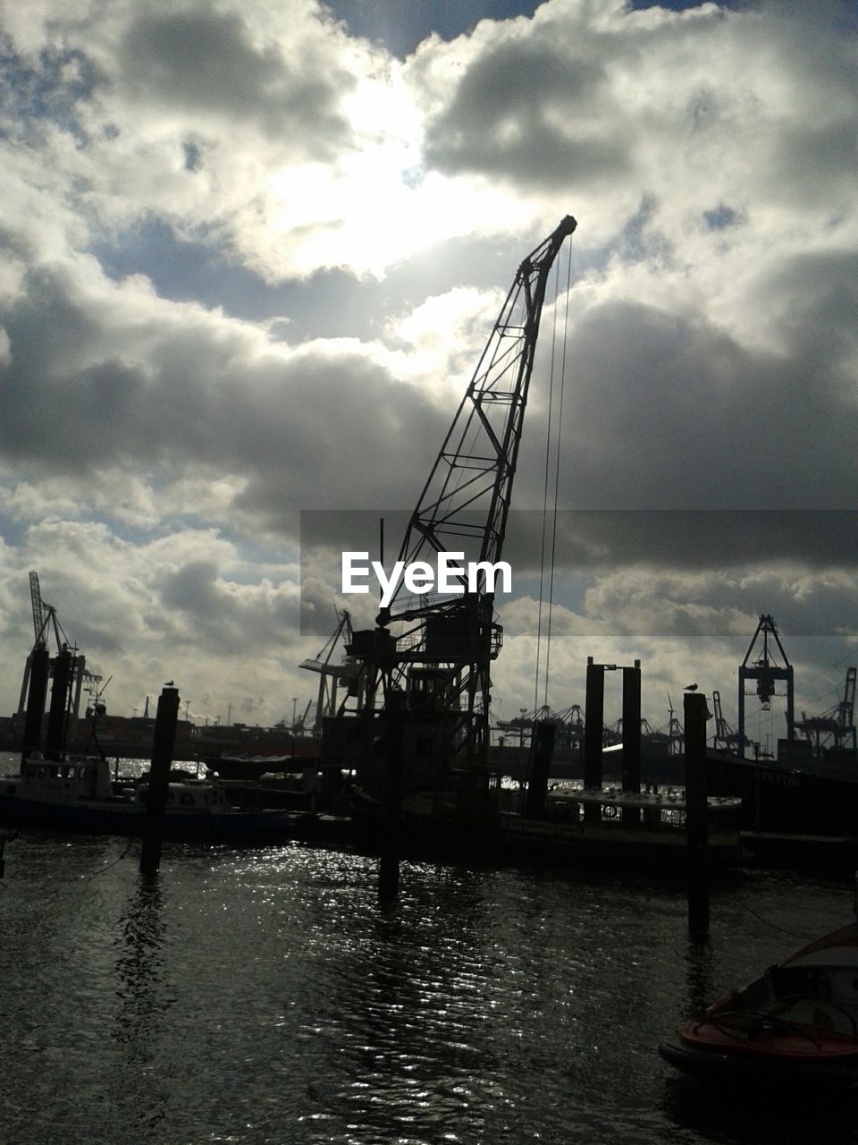 cloud - sky, sky, nautical vessel, water, transportation, waterfront, mode of transport, harbor, outdoors, commercial dock, crane - construction machinery, crane, silhouette, river, no people, day, nature, moored, mast, architecture, shipyard