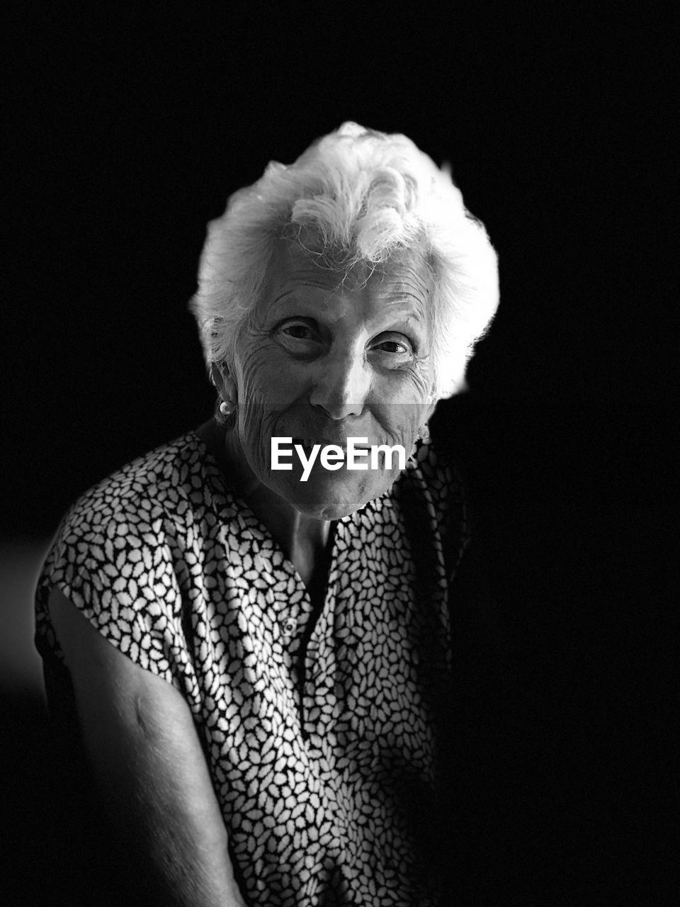 Portrait Of Smiling Senior Woman Against Black Background
