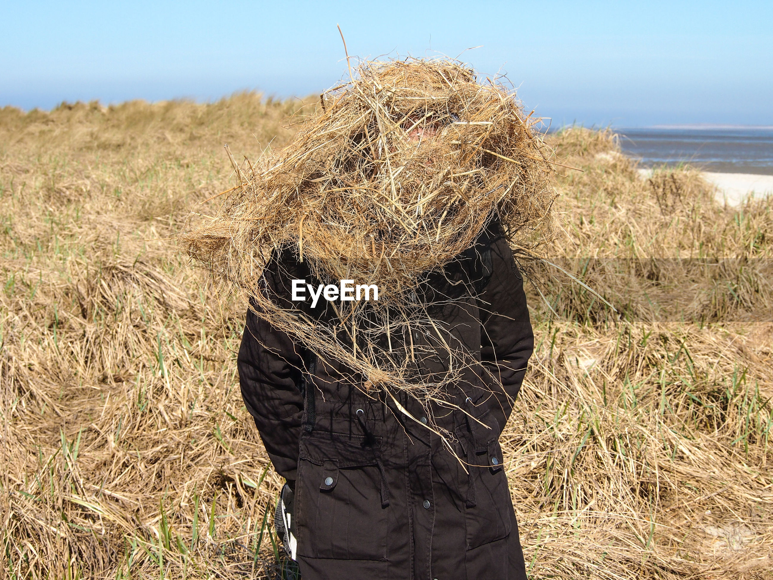 Mature woman face covered with hays standing on land