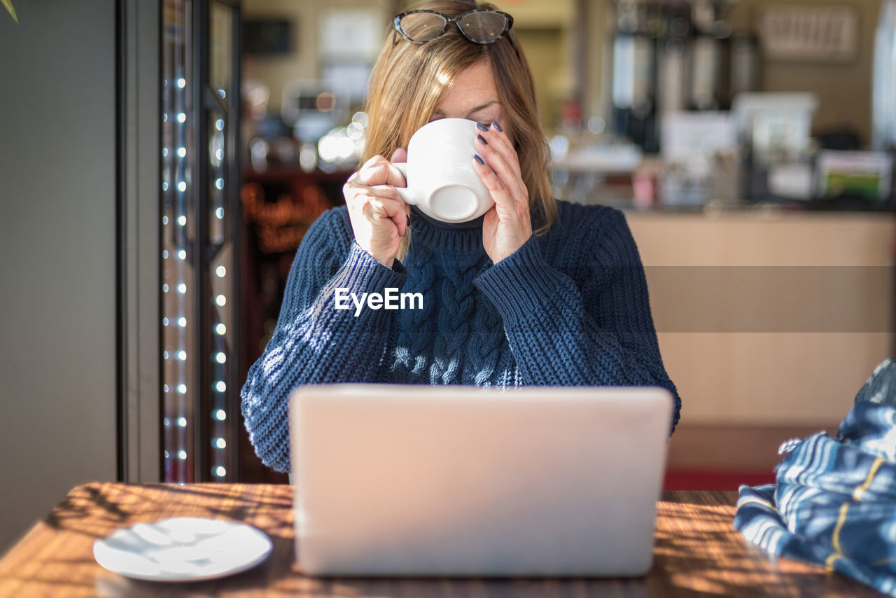 Woman drinking coffee by laptop at table in home