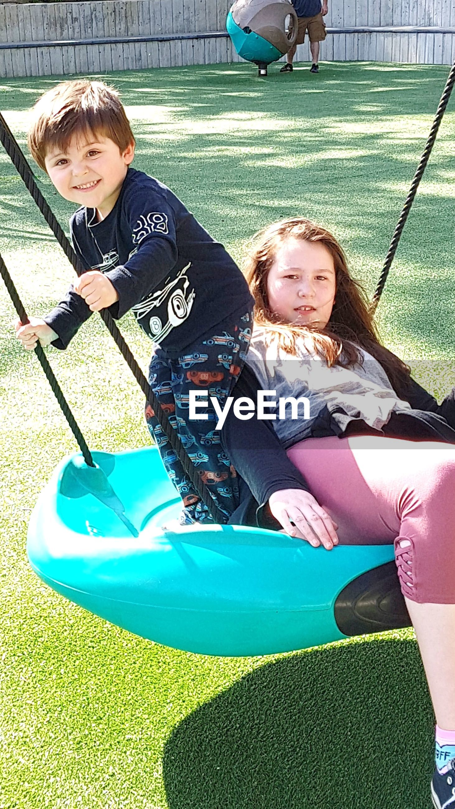 Portrait of siblings playing on swing at playground