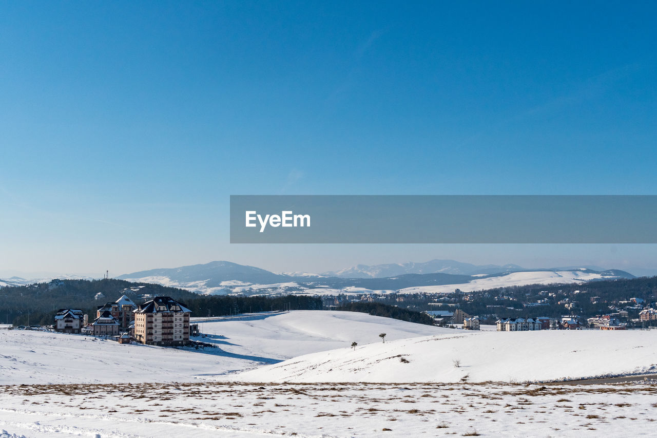 snow, winter, sky, cold temperature, architecture, scenics - nature, mountain, built structure, building exterior, nature, beauty in nature, blue, copy space, white color, tranquil scene, land, clear sky, environment, mountain range, no people, snowcapped mountain, ski resort