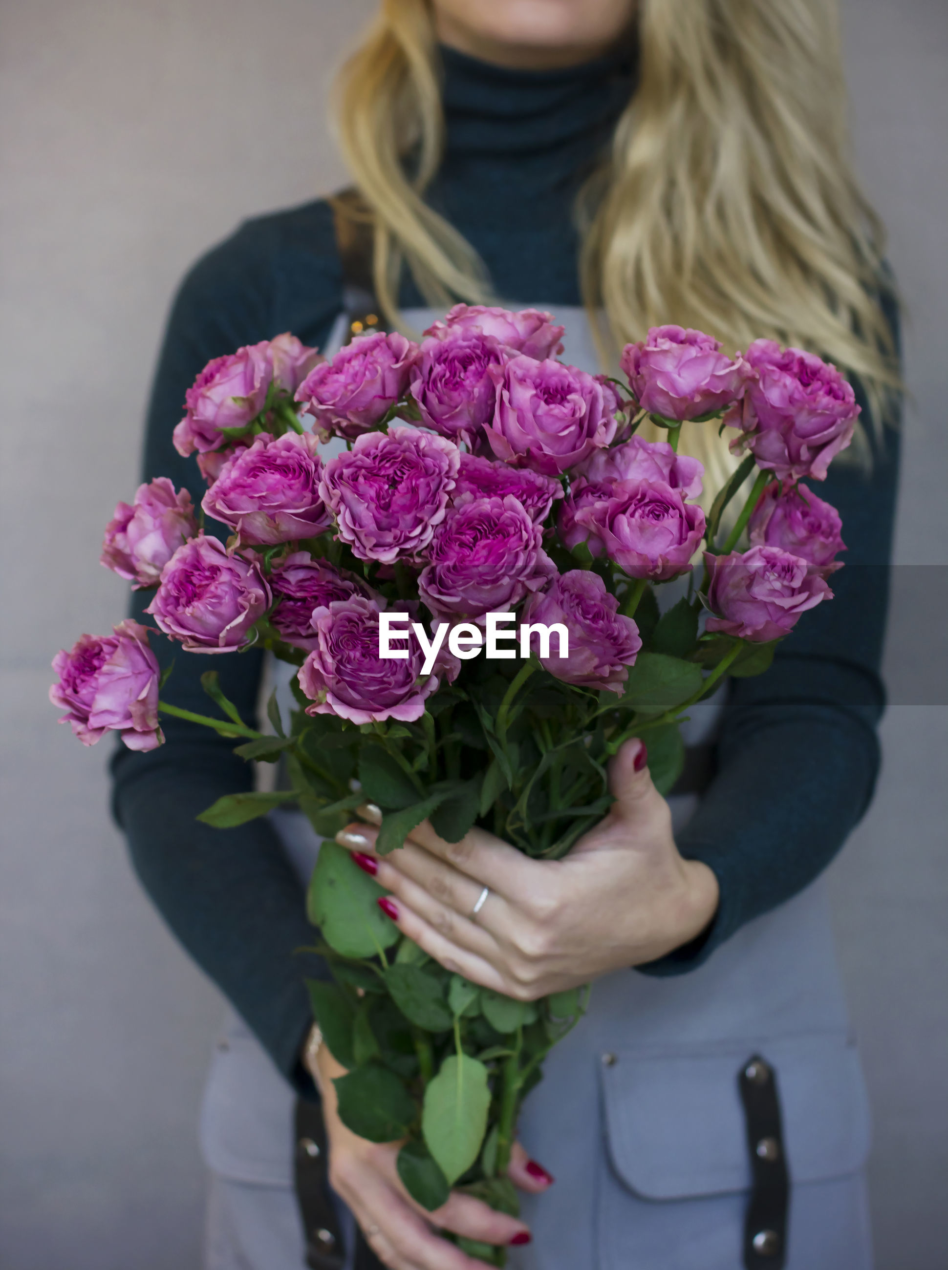 Midsection of woman holding purple flowers