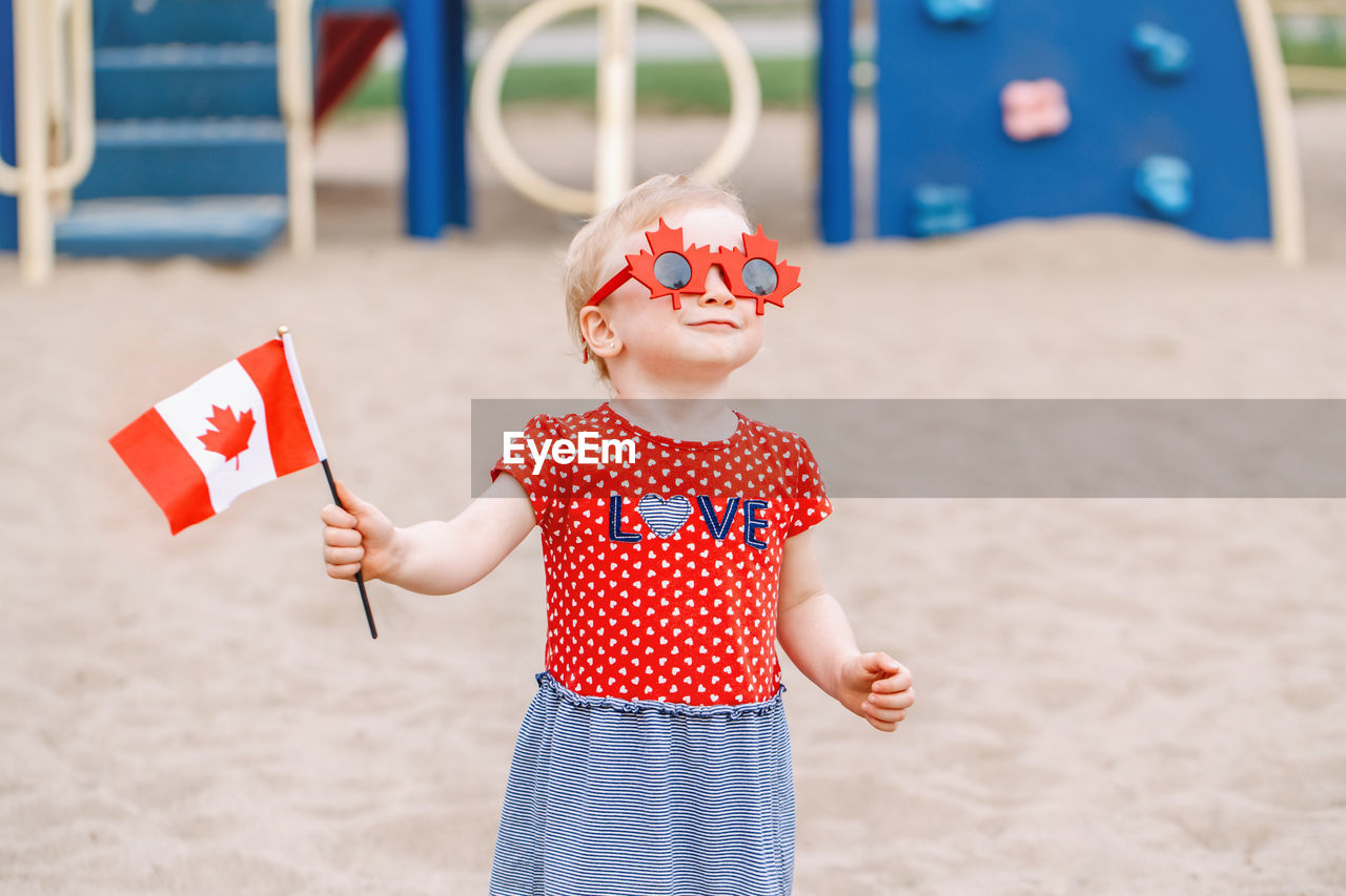 Cute girl wearing sunglasses while holding flag on sand