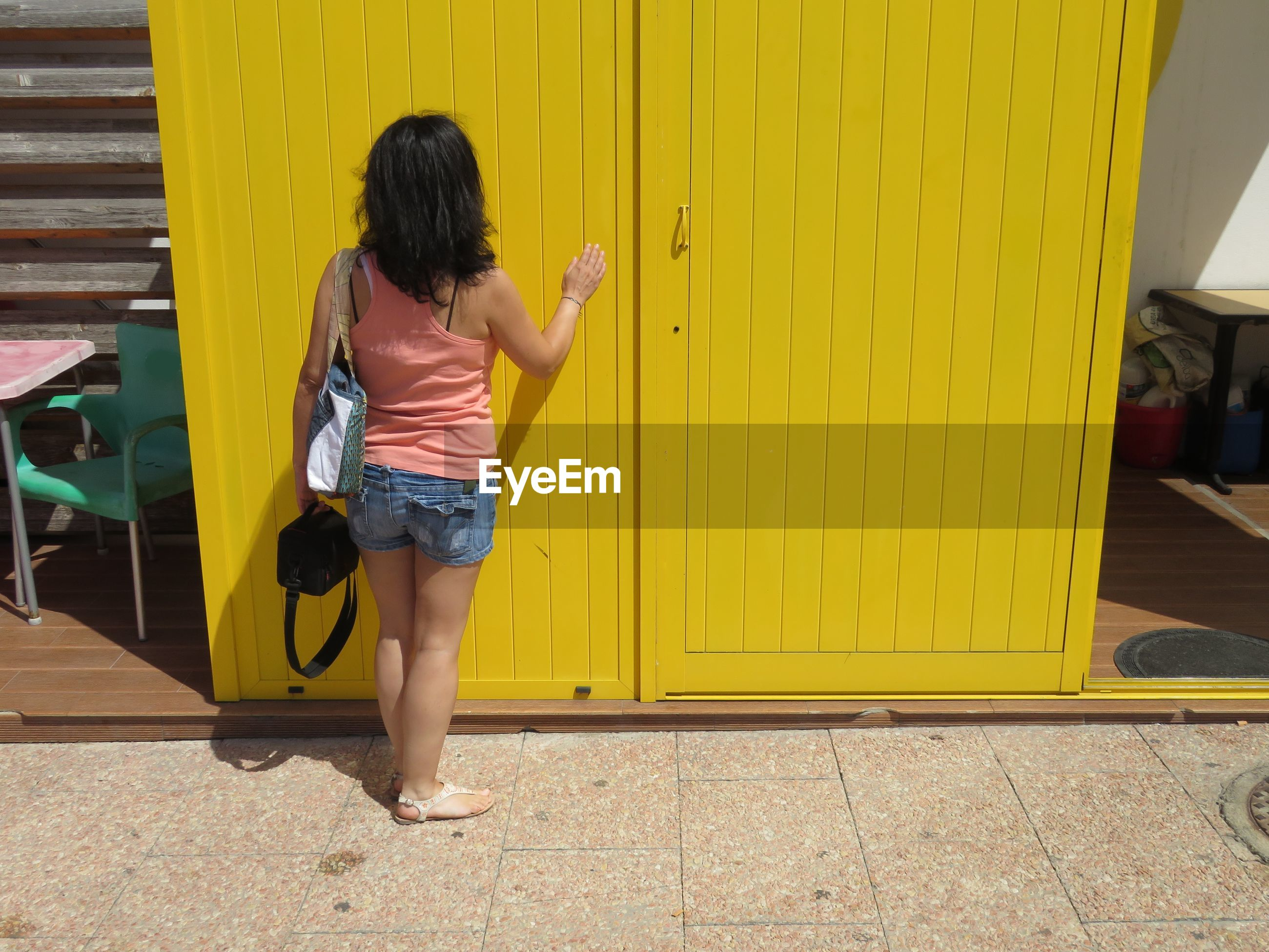 Rear view of woman standing by yellow door