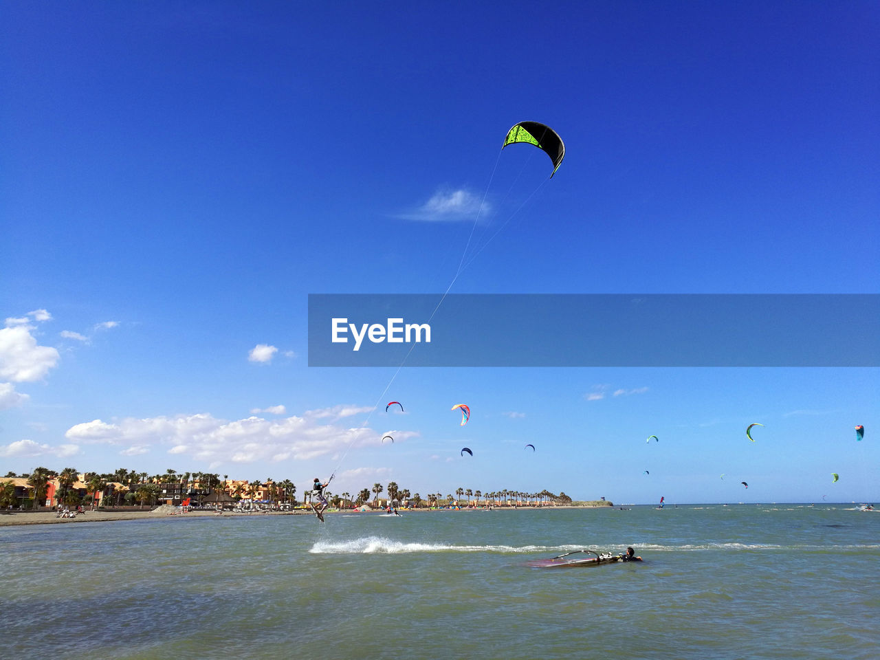 adventure, water, sky, extreme sports, sport, sea, leisure activity, real people, lifestyles, parachute, paragliding, flying, nature, waterfront, day, motion, beauty in nature, trip, beach, kiteboarding, freedom, parasailing, outdoors, wind, horizon over water