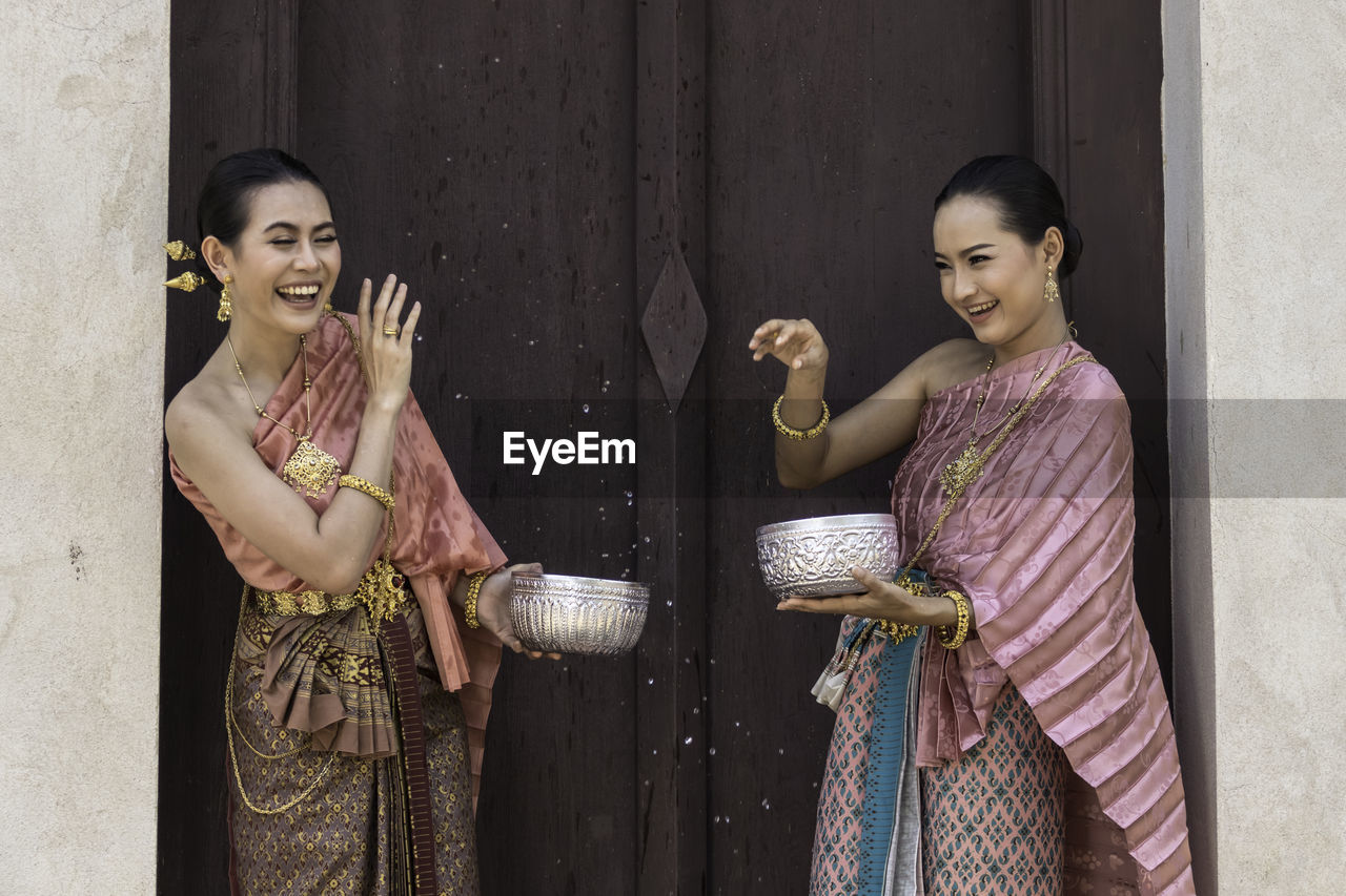 Smiling women wearing traditional clothing holding bowls while standing by wall