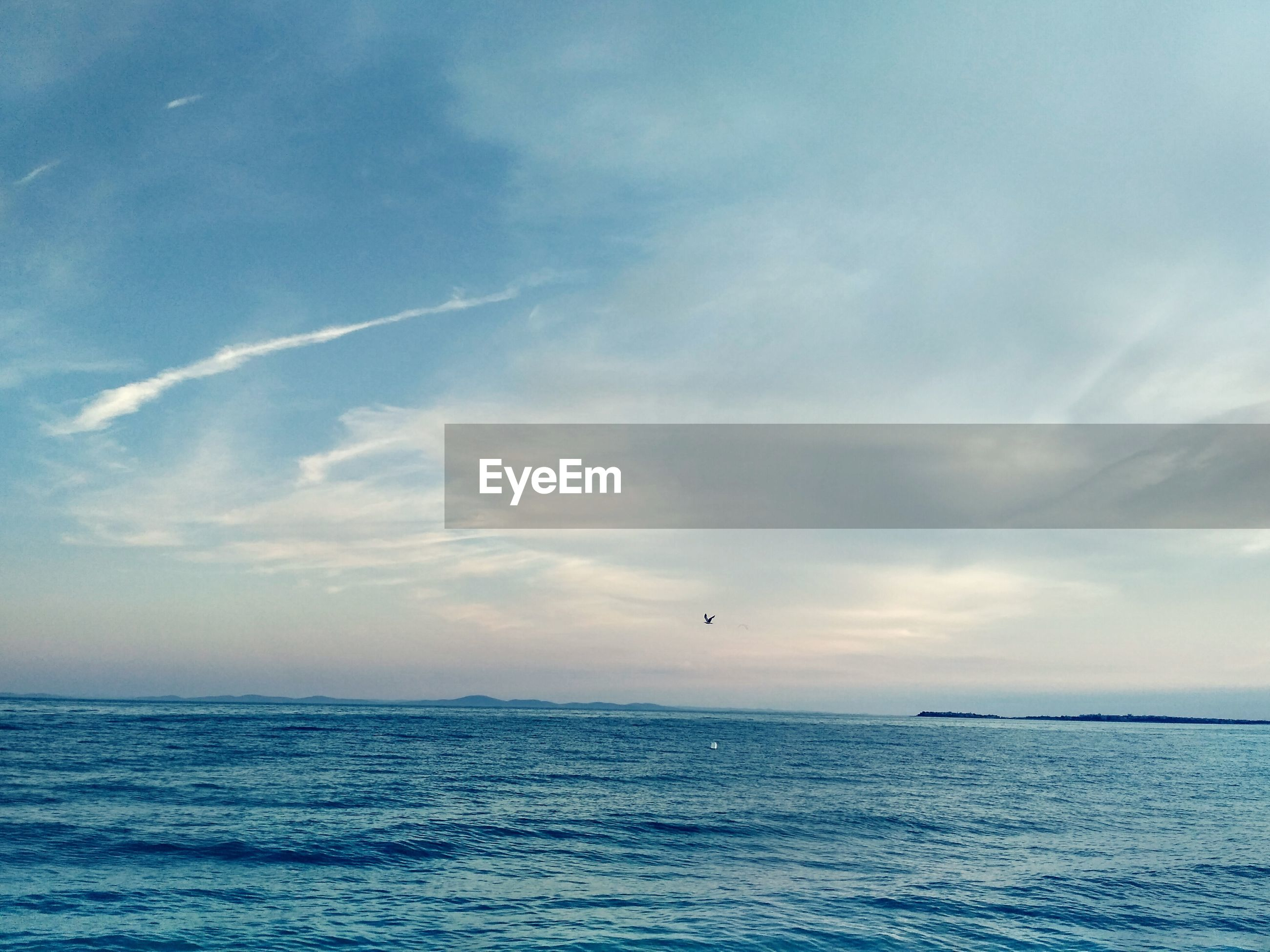 SCENIC VIEW OF SEA AGAINST VAPOR TRAIL IN SKY