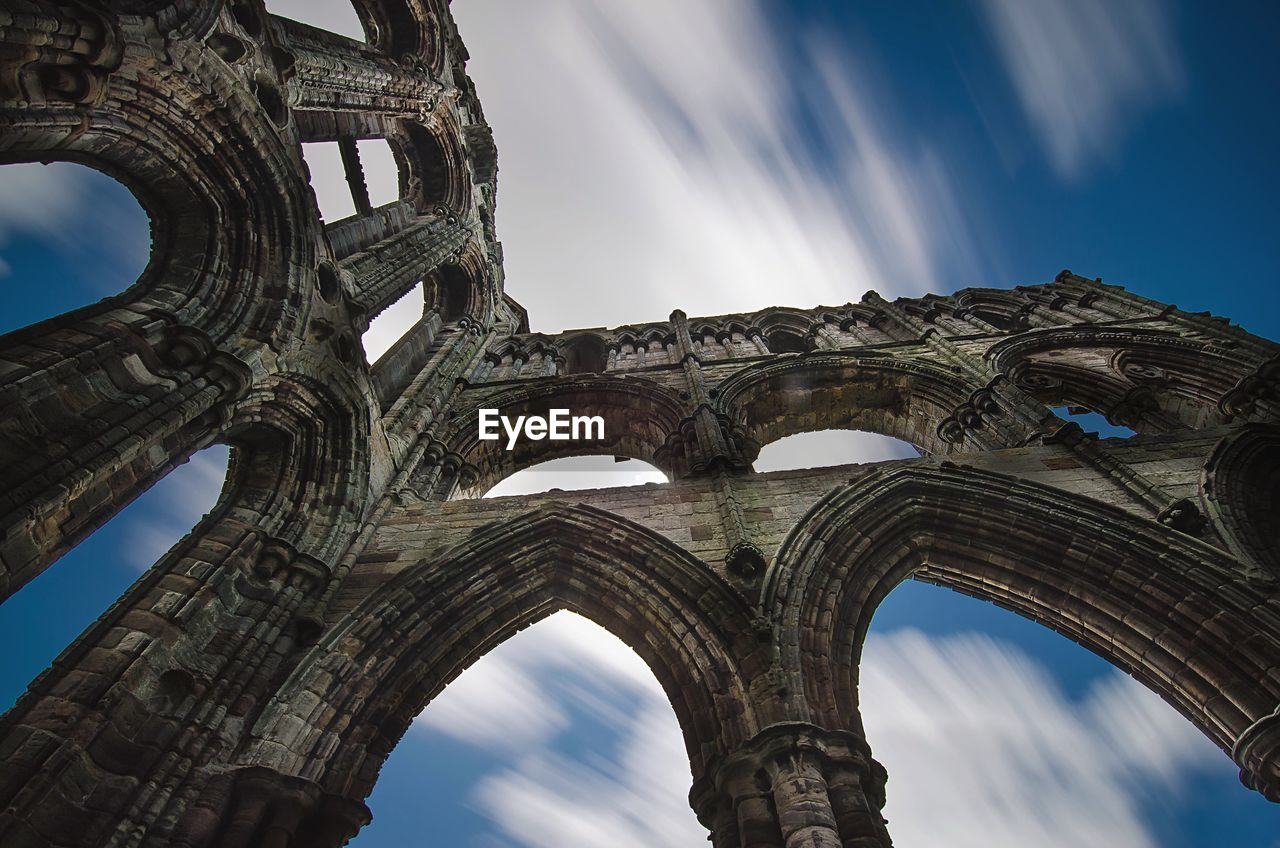 Low angle view of Whitby Abbey against blue sky