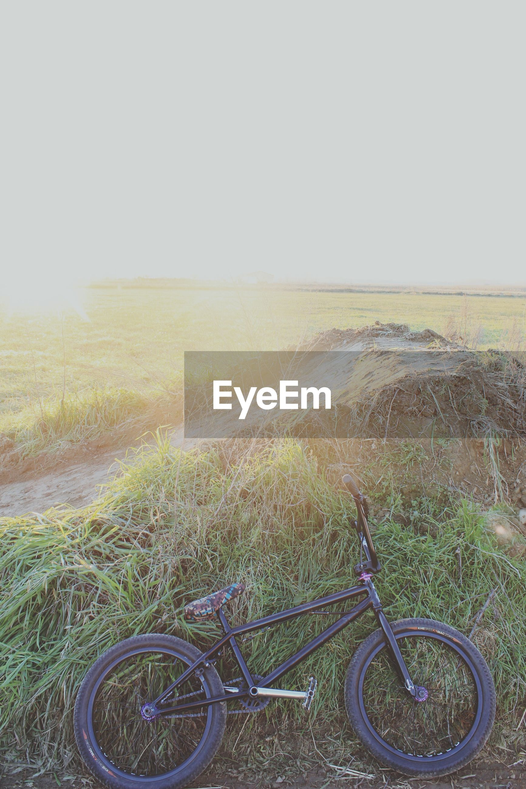bicycle, transportation, land vehicle, mode of transport, landscape, field, tranquility, grass, tranquil scene, stationary, clear sky, beauty in nature, nature, scenics, parked, copy space, parking, plant, growth, day