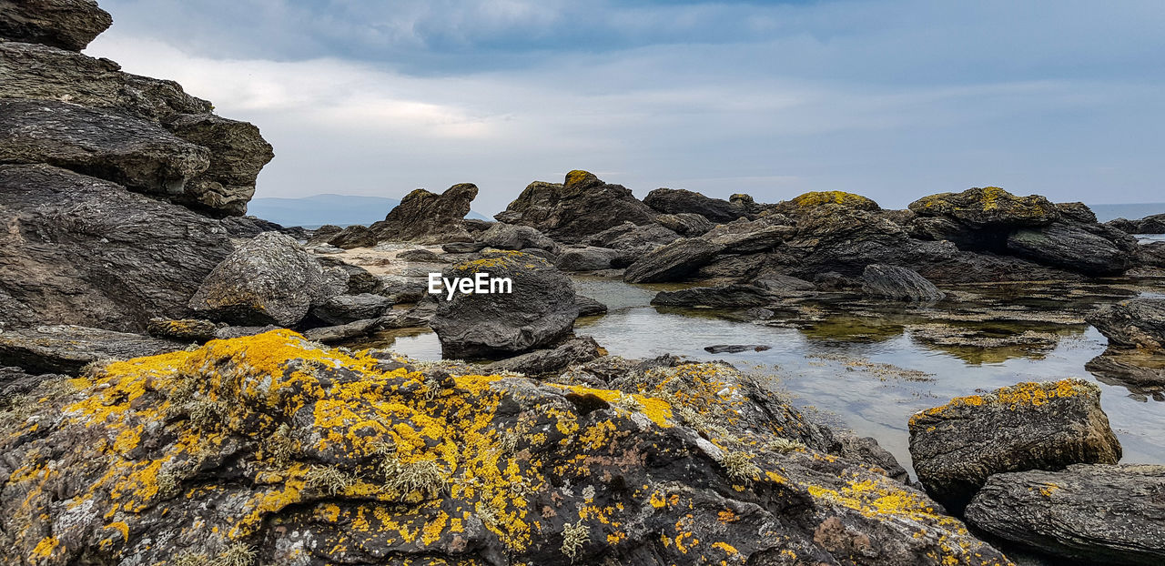 rock, rock - object, solid, sky, beauty in nature, rock formation, cloud - sky, scenics - nature, nature, tranquility, no people, tranquil scene, day, water, non-urban scene, sea, geology, outdoors, rough, lichen, formation, eroded