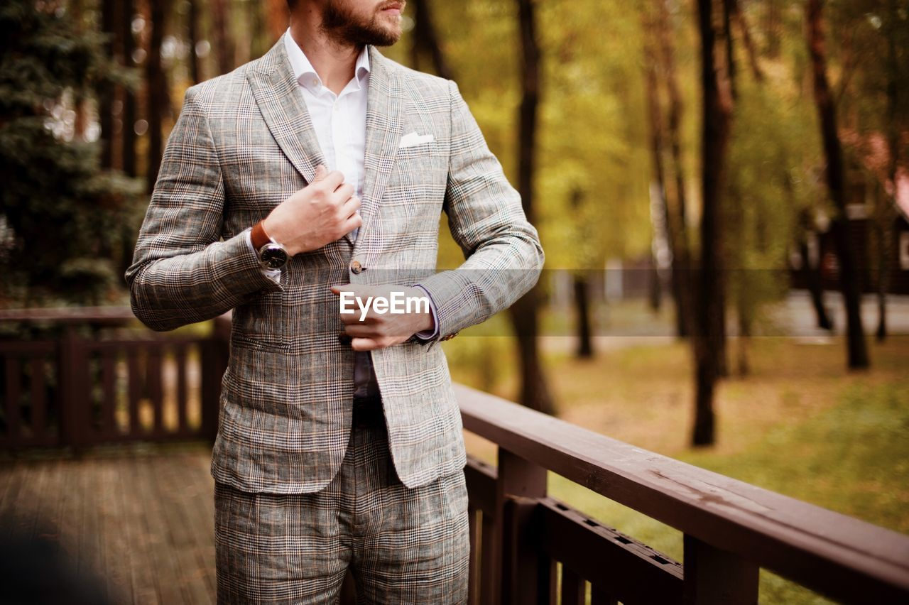 Midsection Of Businessman Wearing Suit Against Trees