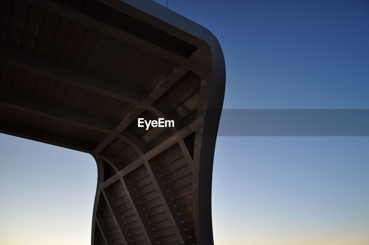 sky, low angle view, built structure, clear sky, architecture, blue, no people, nature, copy space, day, building exterior, outdoors, sunlight, architectural column, bridge, connection, bridge - man made structure, sunset, transportation