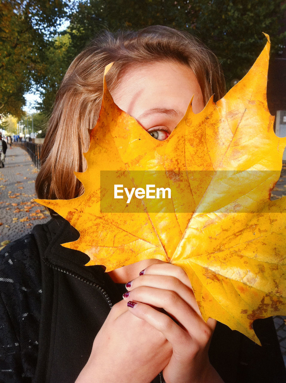 LOW SECTION OF WOMAN STANDING ON YELLOW MAPLE LEAVES