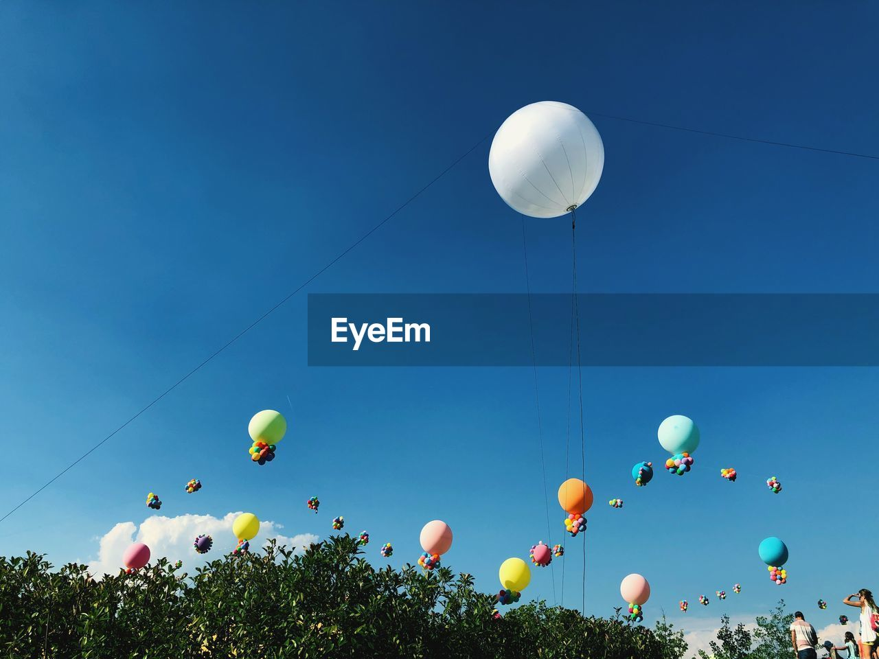 balloon, sky, celebration, low angle view, multi colored, nature, clear sky, day, helium balloon, blue, flying, no people, mid-air, string, sunlight, decoration, outdoors, event, white color, vulnerability, ballooning festival