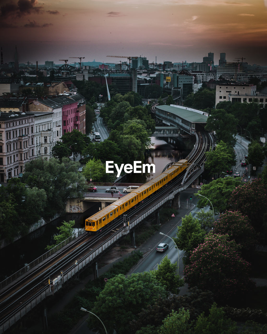 High angle view of train on railway bridge in city during sunset