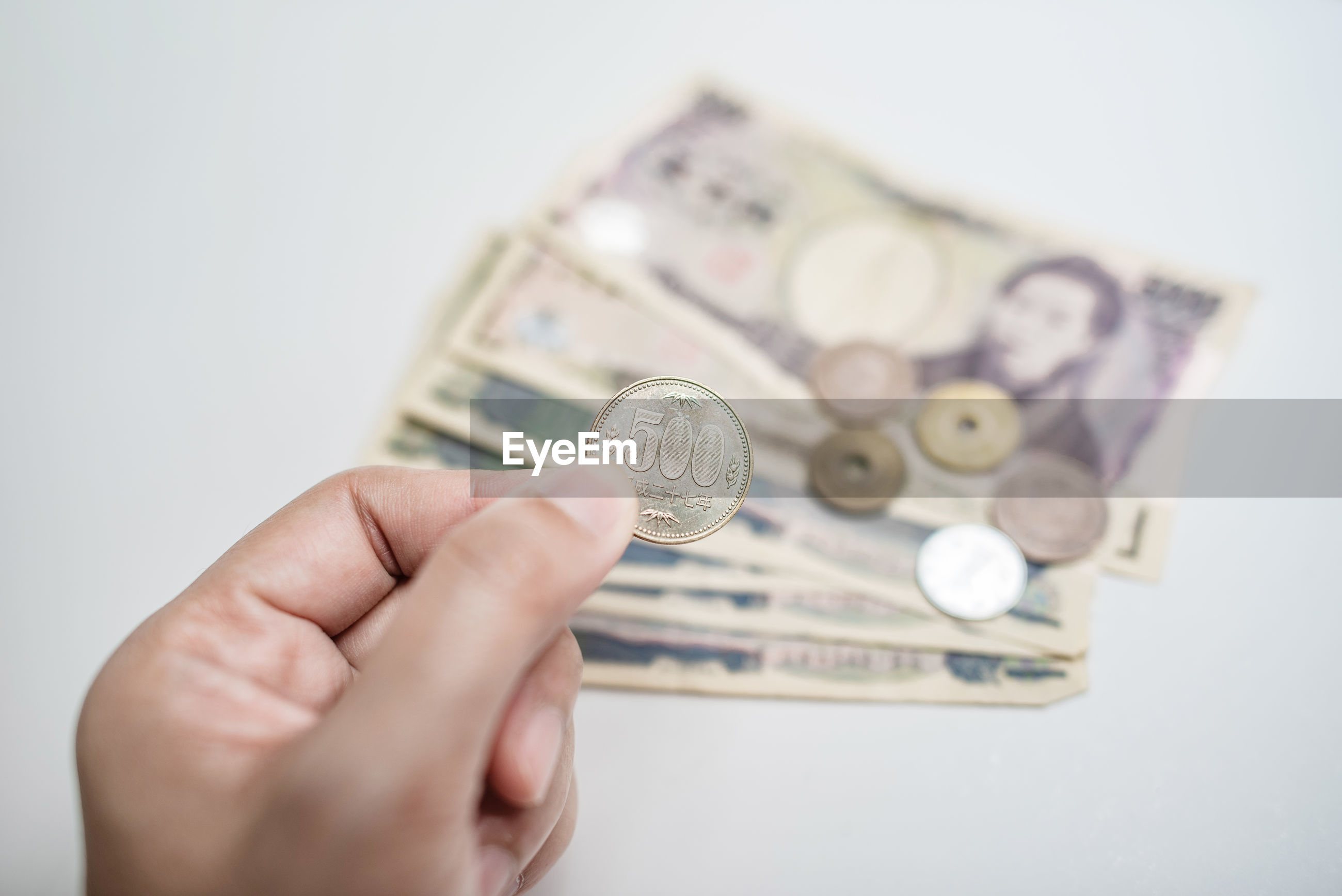 Cropped hand of person holding currency against white background