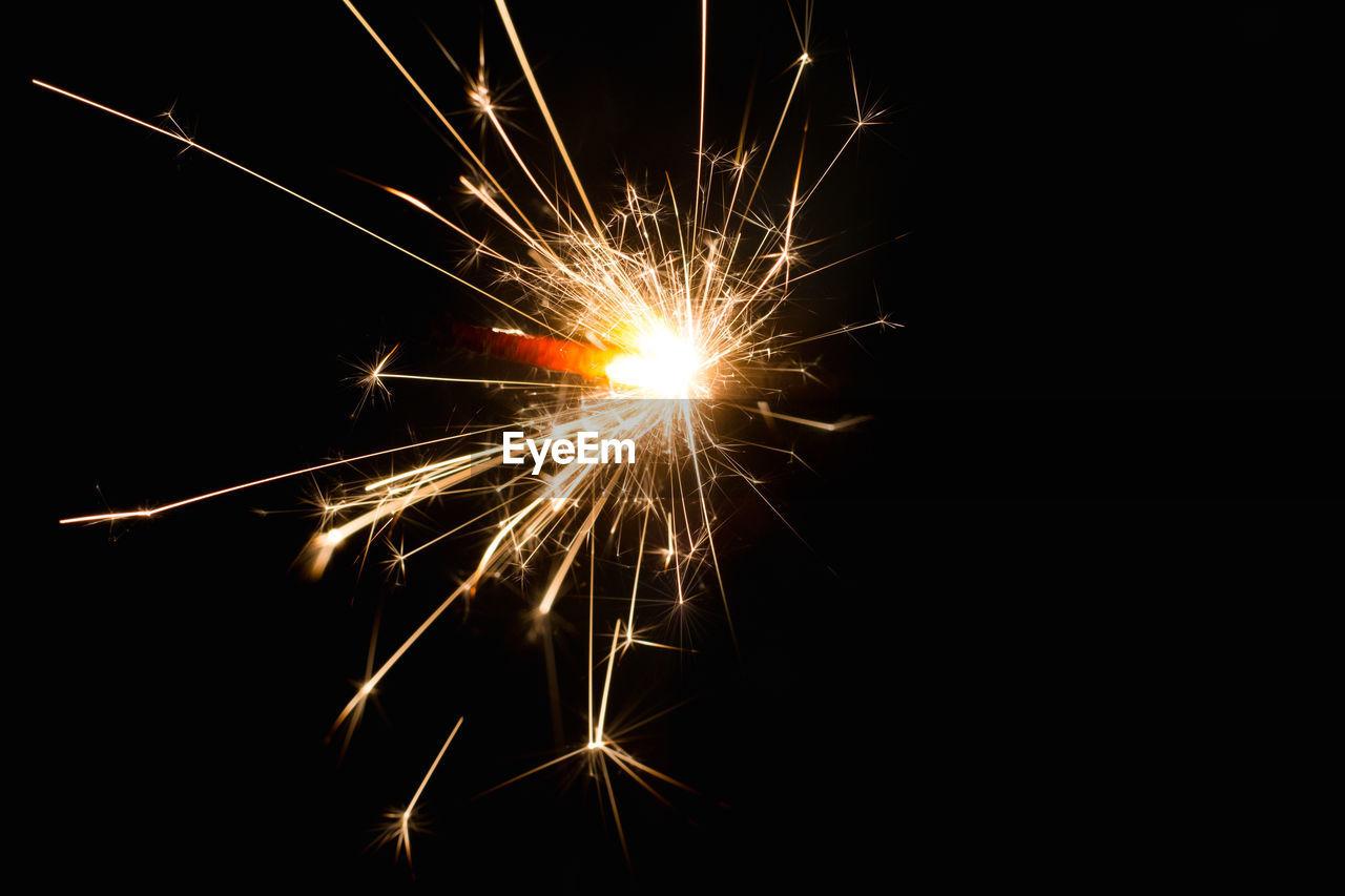 Lit sparkler against black background