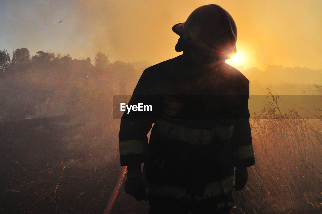 Firefighter Walking On Field Against Sky During Sunset