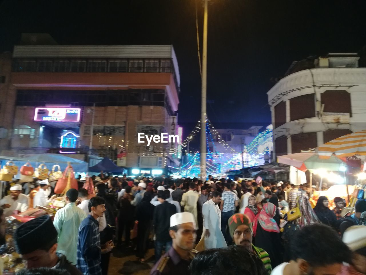 crowd, illuminated, large group of people, night, group of people, architecture, real people, built structure, city, men, building exterior, women, adult, lifestyles, city life, street, leisure activity, motion, outdoors, nightlife