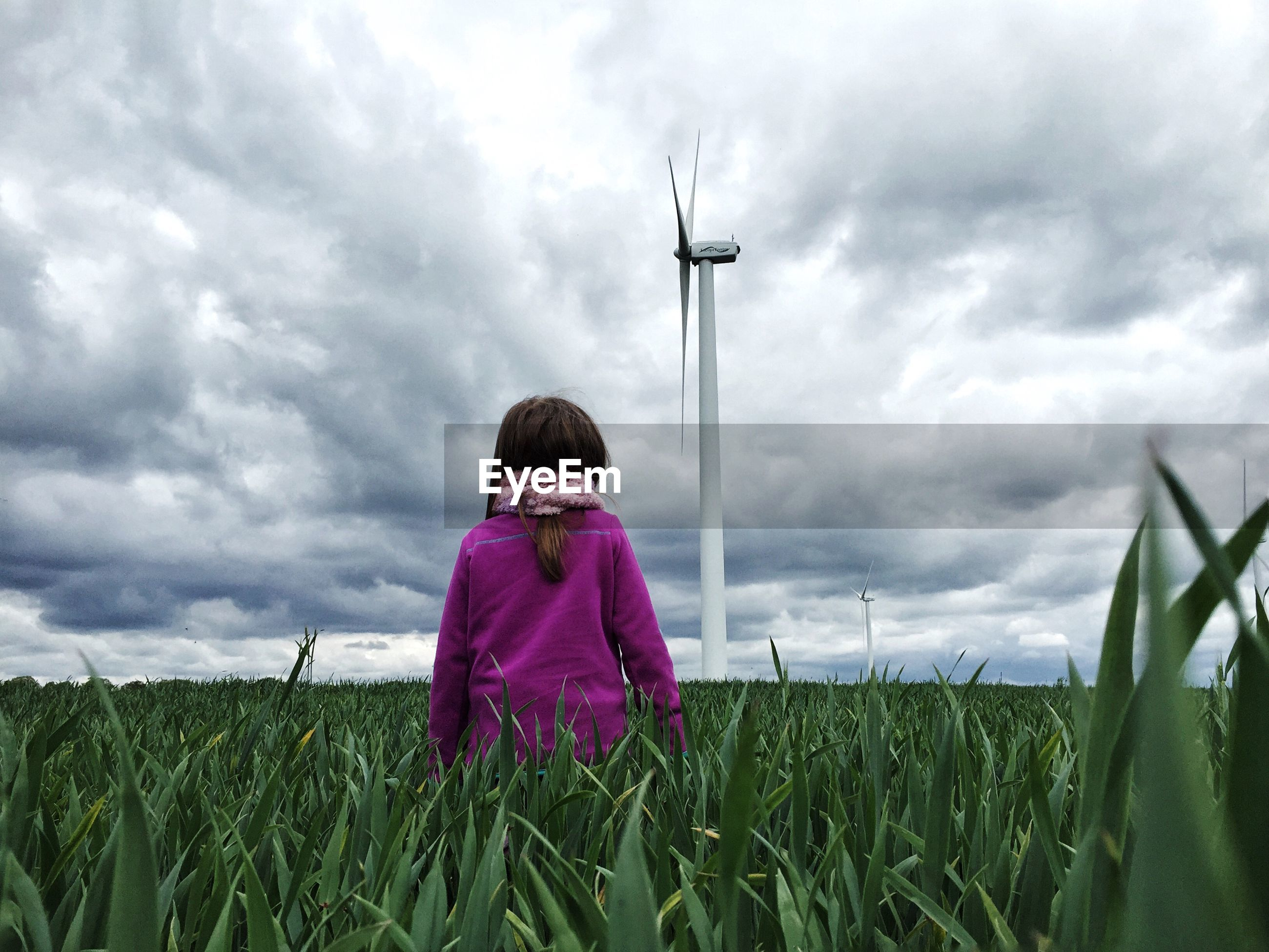 Rear view of girl standing looking at wind turbine on field