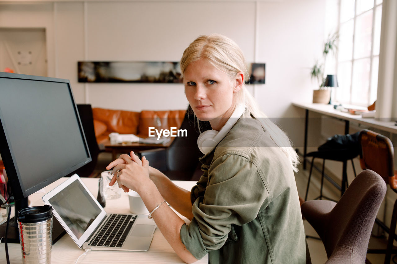 computer, technology, wireless technology, laptop, connection, young adult, young women, sitting, indoors, communication, looking at camera, real people, using laptop, one person, portrait, women, casual clothing, table, three quarter length, beautiful woman, surfing the net
