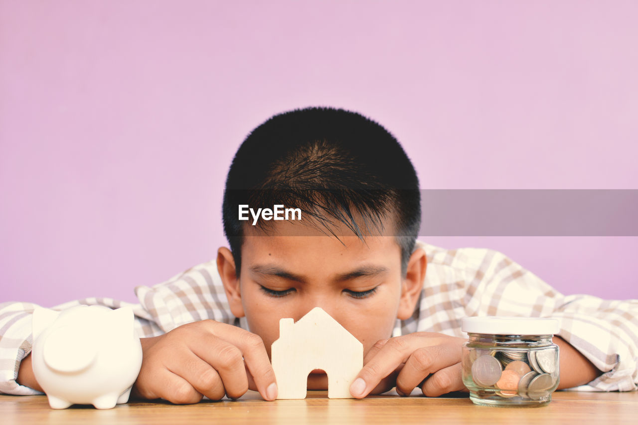Close-Up Of Boy Holding Model Home By Piggy Bank At Table Against Wall