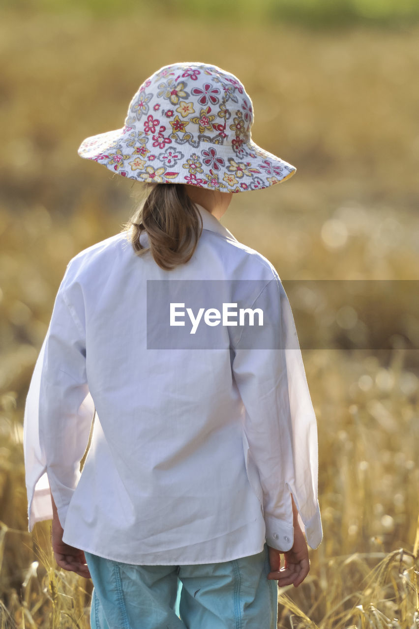 Rear view of girl wearing hat while standing on field