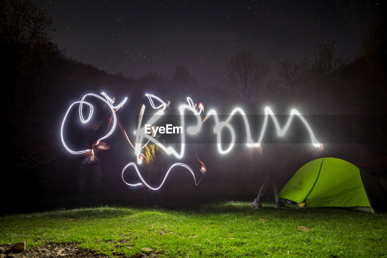 night, illuminated, glowing, light painting, grass, communication, long exposure, text, field, plant, motion, land, western script, nature, light - natural phenomenon, no people, creativity, sign, outdoors