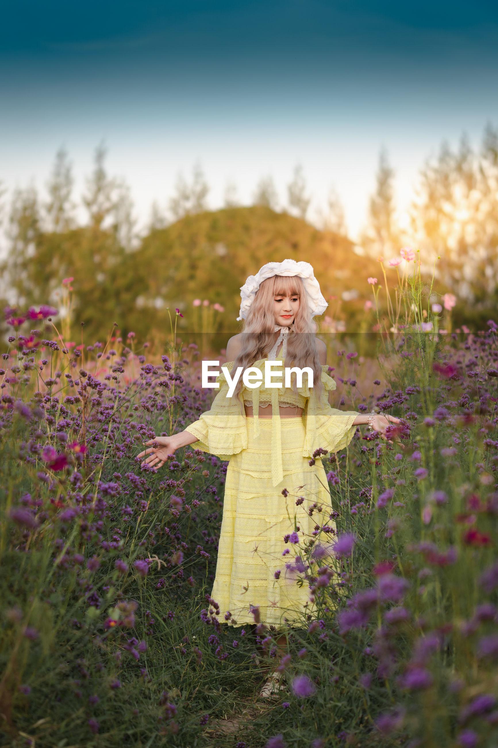 WOMAN STANDING ON PURPLE FLOWERING PLANT ON FIELD