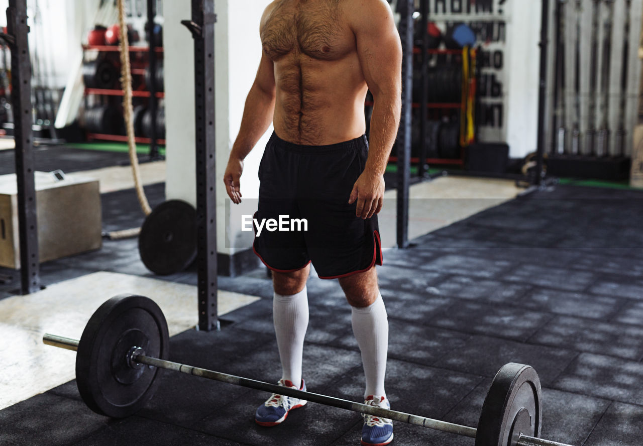 Low Section Of Shirtless Man Standing At Gym