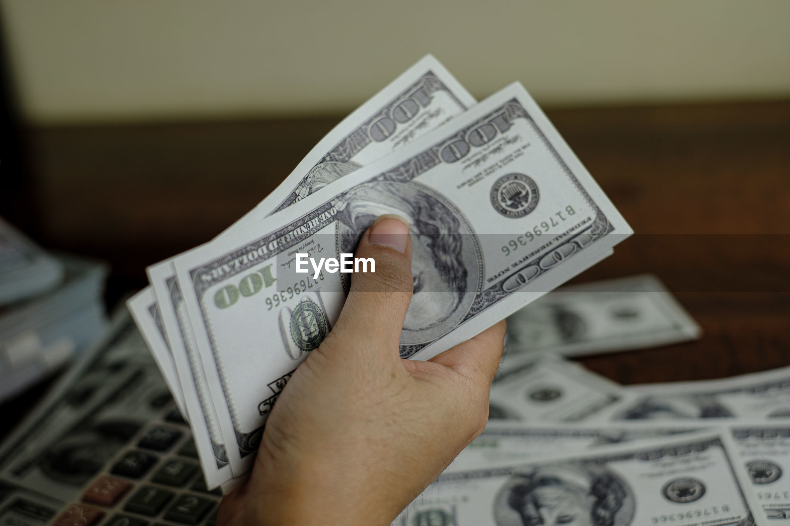 Cropped hand of man holding paper currency at table