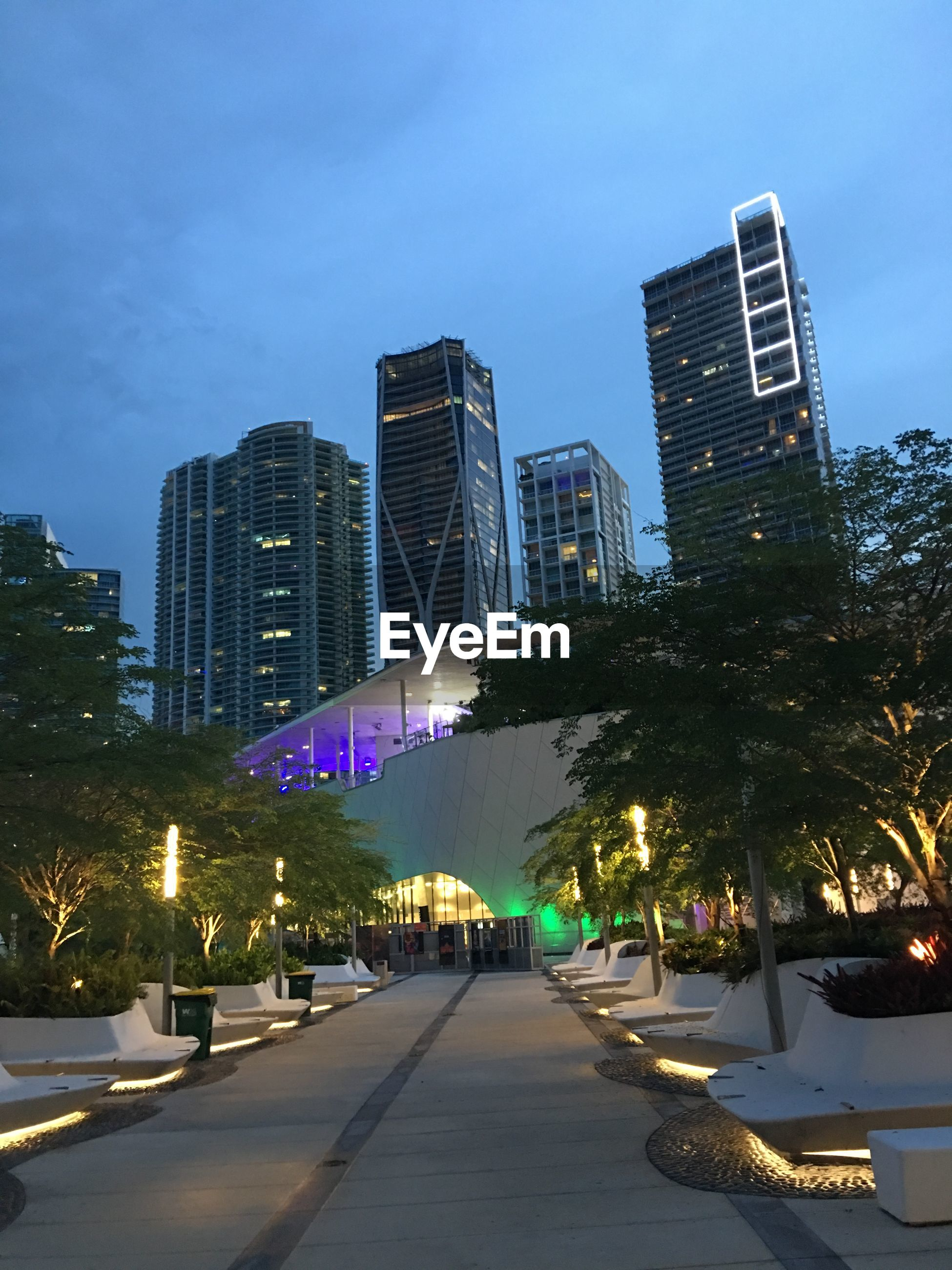 Illuminated footpath against buildings and sky at dusk