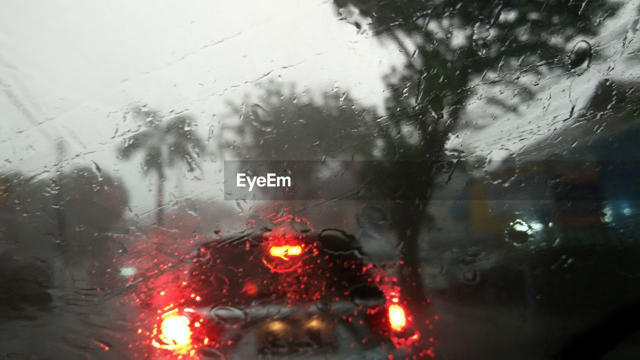 glass - material, car, transparent, land vehicle, vehicle interior, weather, car interior, wet, window, rain, transportation, mode of transport, windshield, rainy season, raindrop, drop, no people, looking through window, water, illuminated, car point of view, road, nature, red, day, indoors, sky, close-up