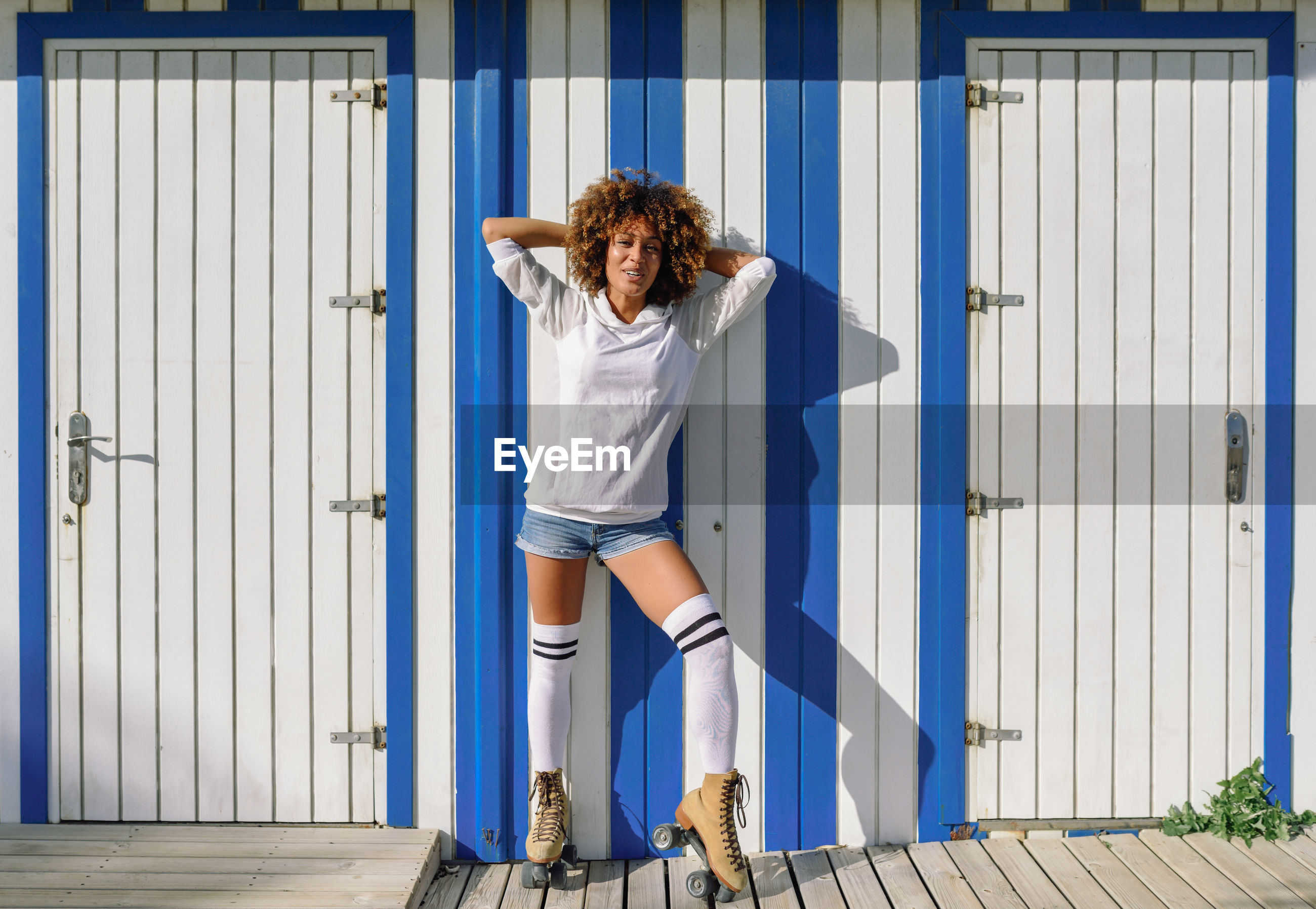Portrait of woman with roller skates standing amidst white doors