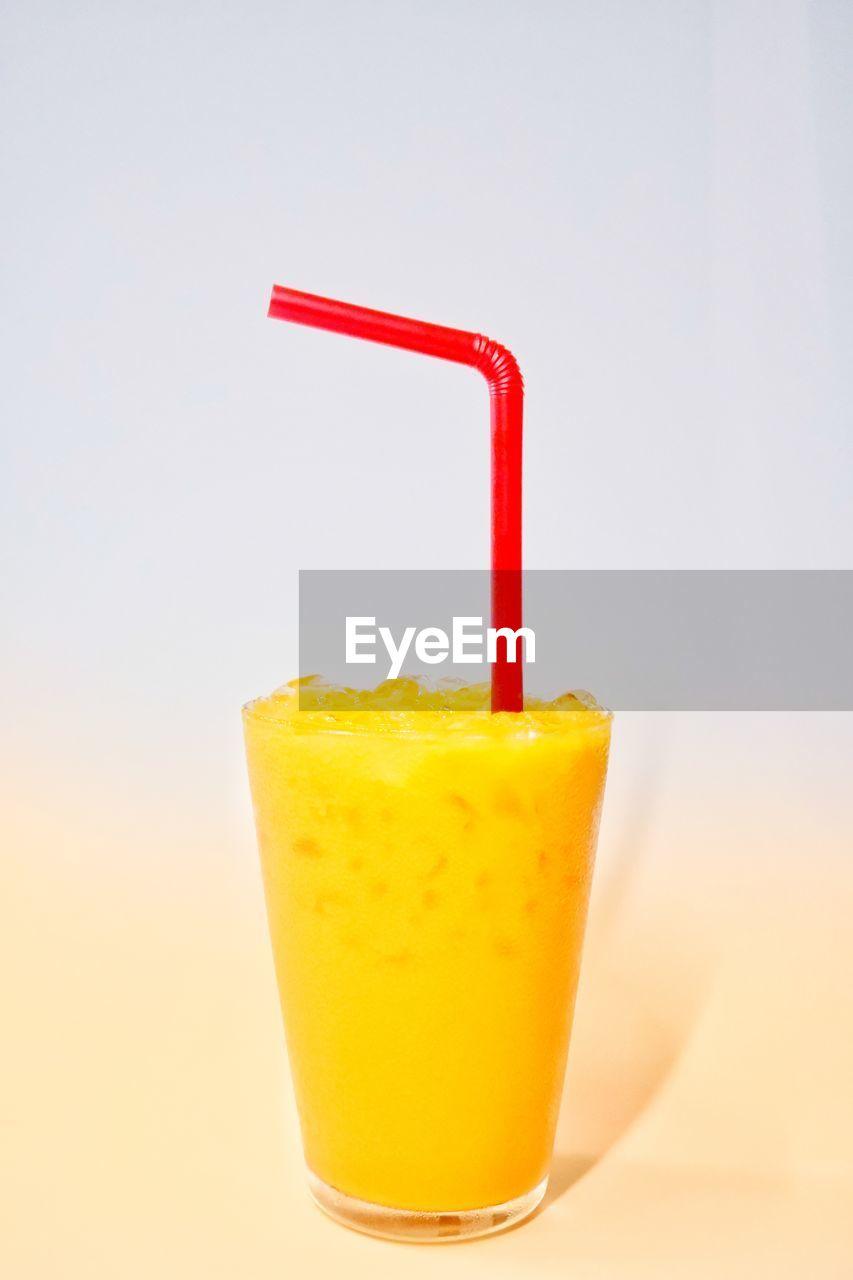 CLOSE-UP OF ORANGE JUICE AGAINST GLASS