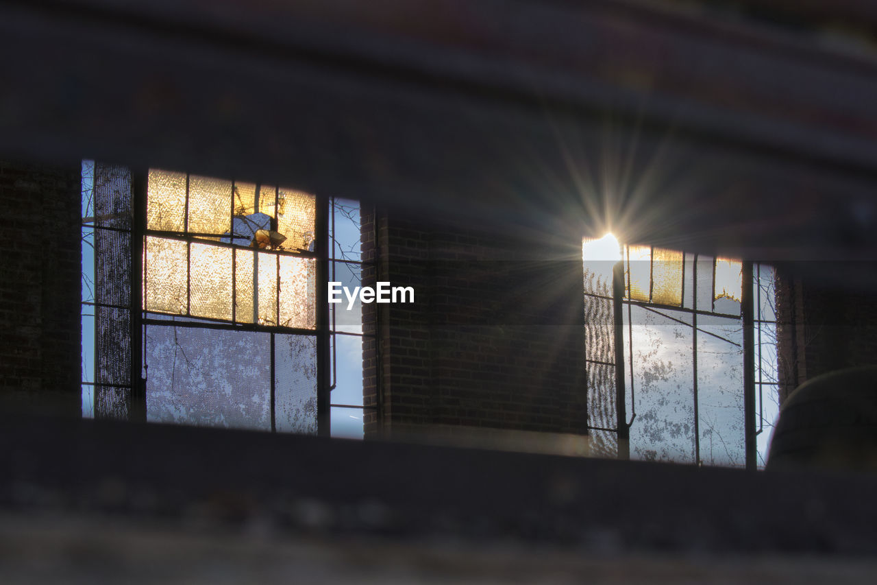 window, indoors, built structure, architecture, sun, no people, illuminated, low angle view, sunset, day