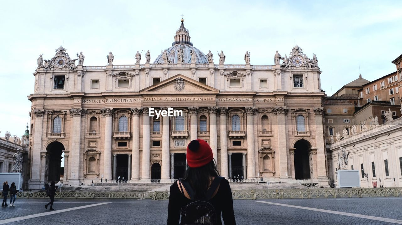Rear View Of Woman Standing In Front Of St Peters Basilica
