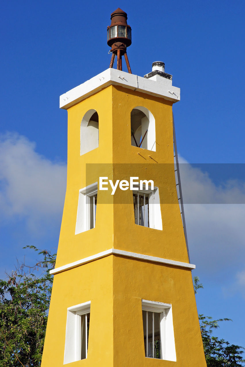low angle view, architecture, built structure, building exterior, sky, yellow, religion, bell tower, day, window, place of worship, spirituality, outdoors, blue, no people, sunlight, cloud - sky, cross