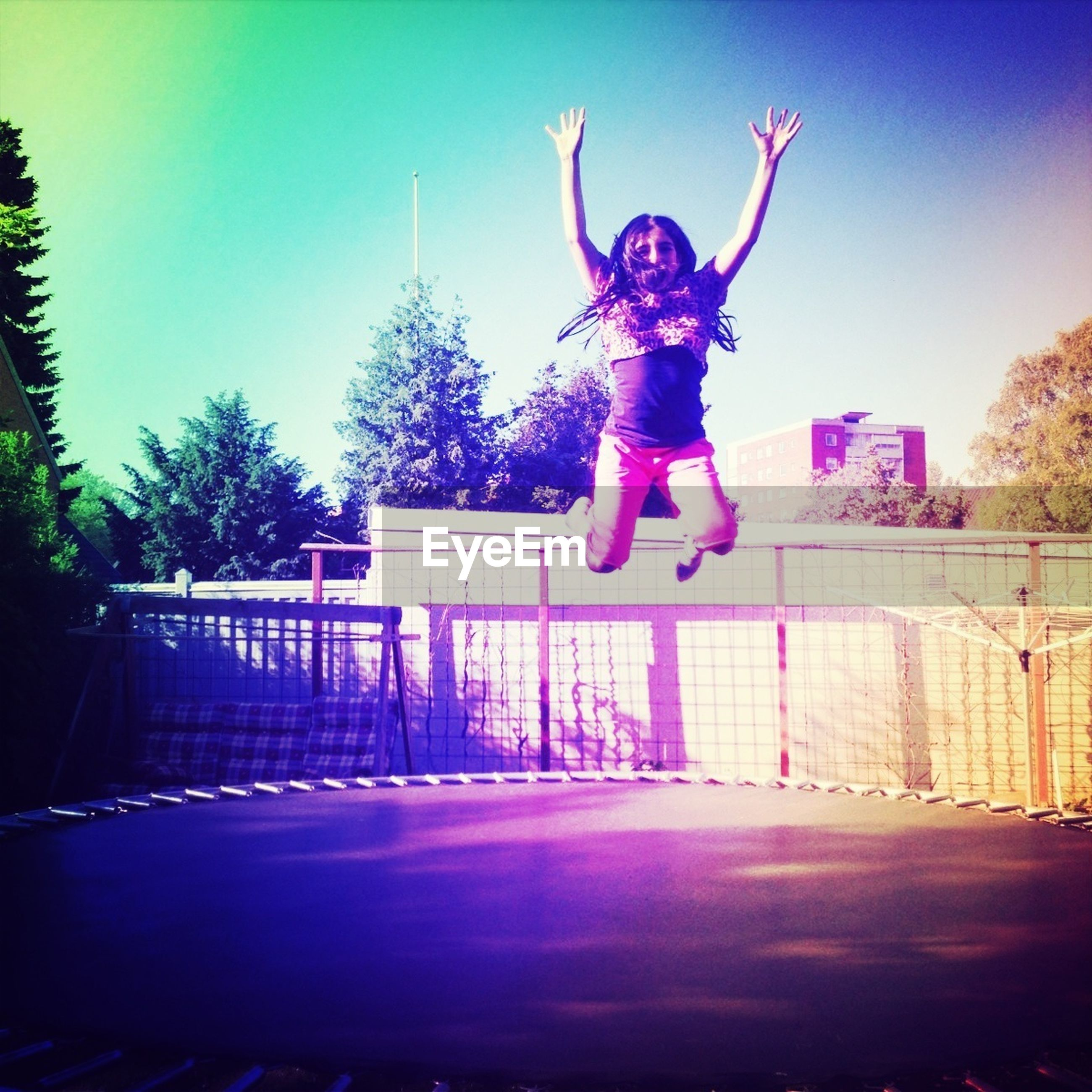 full length, lifestyles, leisure activity, young adult, person, jumping, casual clothing, mid-air, built structure, clear sky, architecture, fun, enjoyment, motion, front view, blue, sunlight, arms outstretched